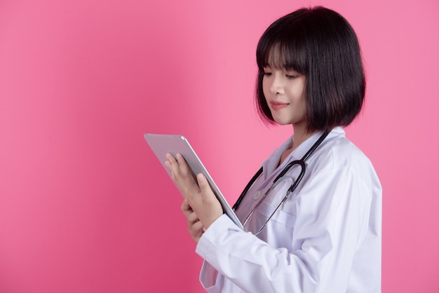 Azjatycki lekarz kobieta z białym fartuchu na różowo