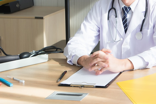Azjatycki lekarz, lekarz tajski, zawiesił stetoskop na szyi, czekając, aż pacjent przyjdzie i sprawdzi chorobę przy biurku w szpitalnym gabinecie