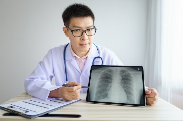 Azjatycki lekarz mężczyzna pracuje w szpitalu biurowym. omawianie zdjęć rentgenowskich za pomocą cyfrowego tabletu.