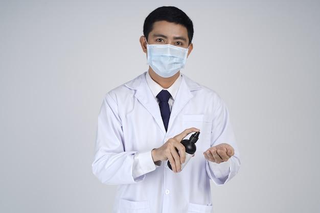 Azjatycki lekarz mężczyzna w masce medycznej, pokazując butelkę produktu