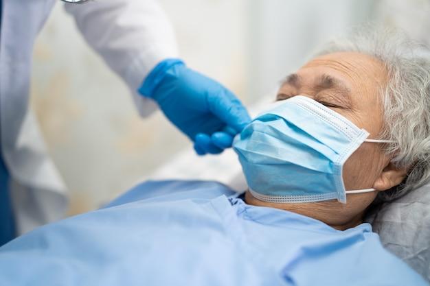 Azjatycki lekarz noszący kombinezon i rękawice ppe nowy normalny, aby sprawdzić, czy pacjent chroni koronawirusa covid-19.