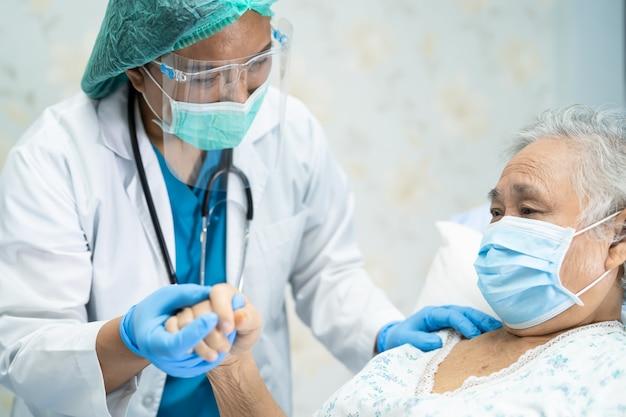 Azjatycki lekarz noszący osłonę twarzy i kombinezon ppe nowy normalny, aby sprawdzić bezpieczeństwo pacjenta. infekcja covid-19 koronawirus na kwarantannie.