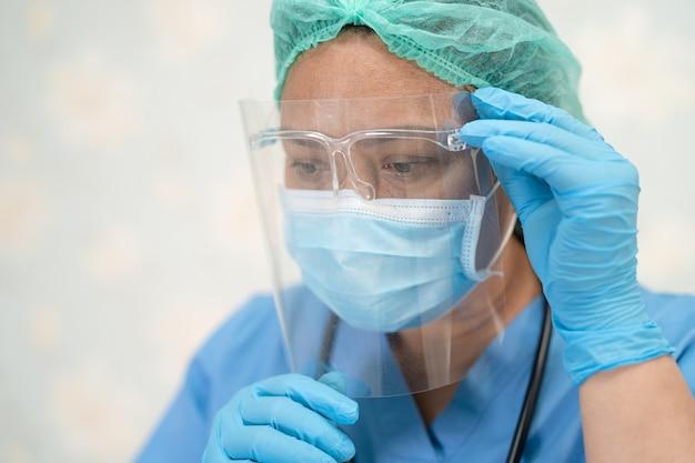 Azjatycki lekarz noszący osłonę twarzy i kombinezon ppe nowy normalny, aby sprawdzić, czy pacjent chroni infekcję bezpieczeństwa covid-19