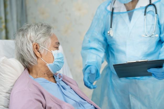 Azjatycki lekarz noszący osłonę twarzy i kombinezon ppe nowy normalny, aby sprawdzić, czy pacjent chroni pacjenta przed zakażeniem. epidemia koronawirusa covid-19 na kwarantannie.