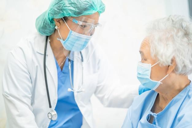 Azjatycki lekarz noszący osłonę twarzy i kombinezon ppe nowy normalny, aby sprawdzić ochronę pacjenta przed koronawirusem covid-19.