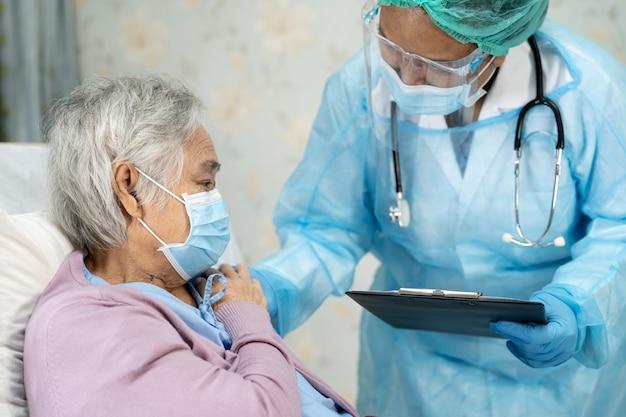 Azjatycki lekarz noszący osłonę twarzy i kombinezon ppe w celu ochrony koronawirusa covid19