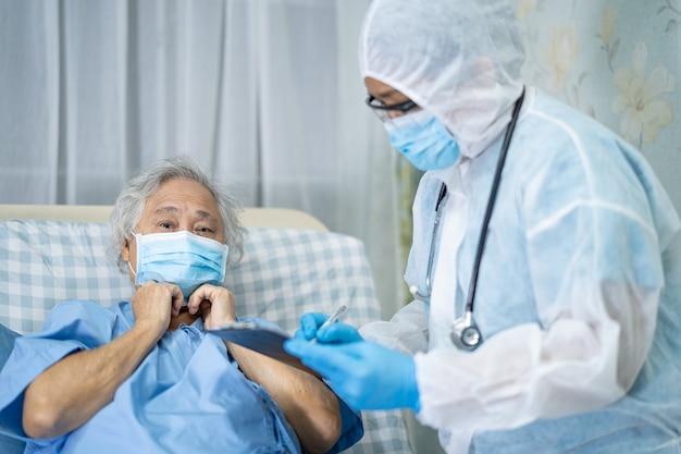 Azjatycki lekarz noszący osłonę twarzy i kombinezon ppe w celu ochrony przed infekcją covid19 coronavirus