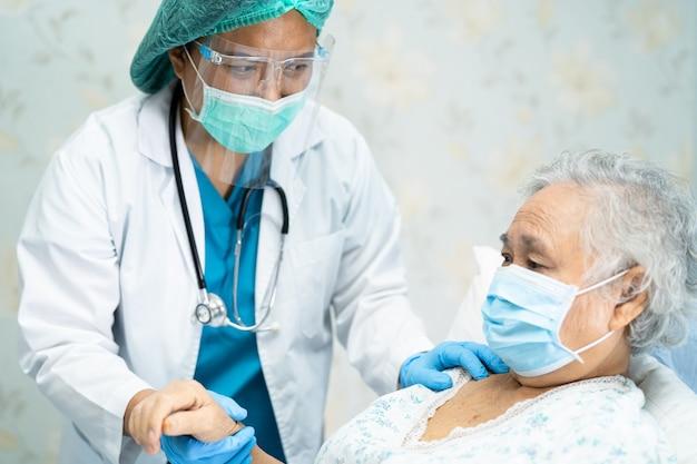 Azjatycki lekarz noszący osłonę twarzy i kombinezon ppe w celu ochrony przed koronawirusem covid