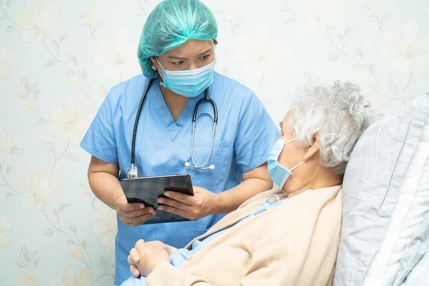 Azjatycki lekarz noszący osłonę twarzy i nowy kombinezon ppe, aby sprawdzić stan pacjenta
