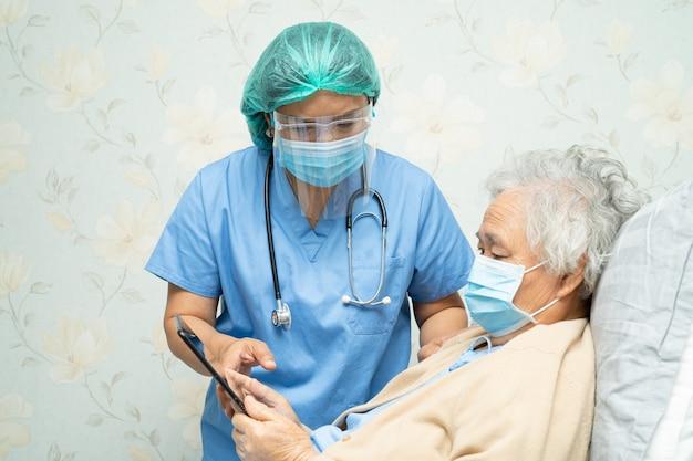 Azjatycki lekarz noszący osłonę twarzy i nowy kombinezon ppe w celu ochrony koronawirusa covid-19.