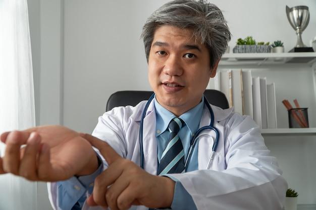 Azjatycki lekarz odwiedza pacjenta online w aplikacji internetowej i notuje objawy oraz wyjaśnia, jak leczyć początkową chorobę