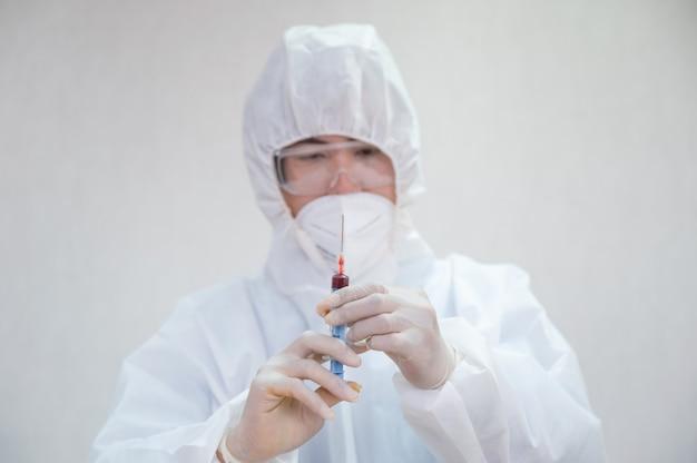 Azjatycki lekarz płci męskiej w medycznej ppe trzymając strzykawkę do wstrzykiwania próbki krwi w laboratorium