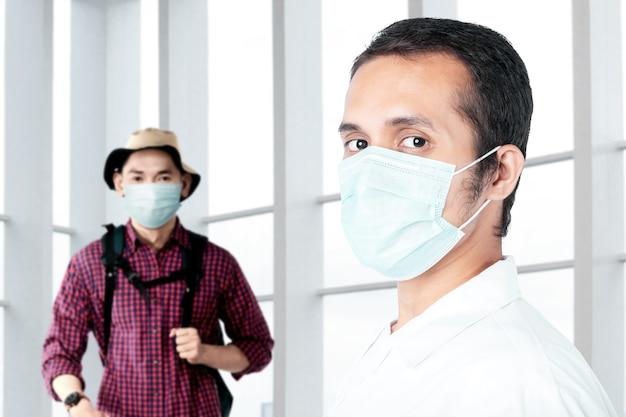 Azjatycki lekarz sprawdzający stan zdrowia człowieka przed podróżą do szpitala. badanie lekarskie przed podróżą