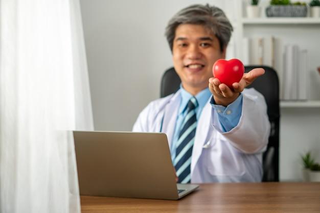 Azjatycki lekarz trzymający zabawkę w kształcie serca i siedzący w swoim gabinecie ze swoim komputerem