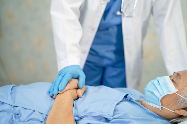 Azjatycki lekarz w kombinezonie ppe, aby sprawdzić pacjenta z maską chroniącą przed koronawirusem covid1919