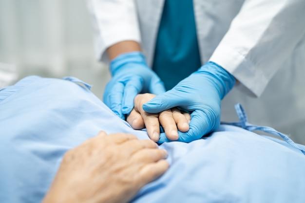 Azjatycki lekarz w rękawiczce chroni koronawirusa covid-19.