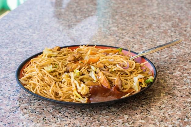 Azjatycki makaron chow mein z mięsem z kurczaka i warzywami. popularne danie kuchni orientalnej. zdjęcie stockowe.