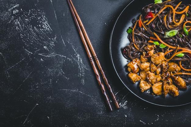 Azjatycki makaron soba, kurczak, warzywa, ciemne tło. miejsce na tekst.