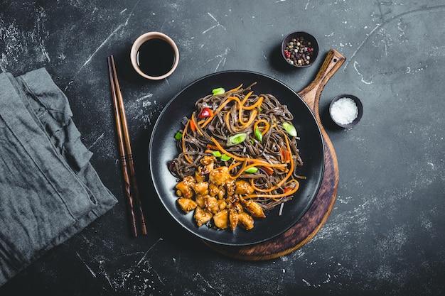 Azjatycki makaron soba, kurczak, warzywa, rustykalne betonowe ciemne tło.