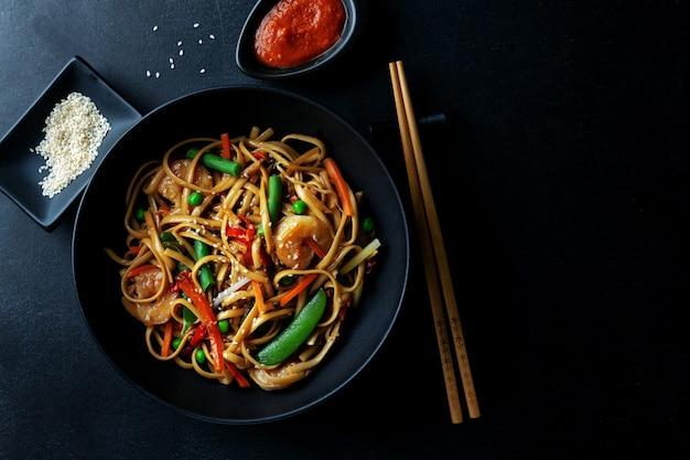 Azjatycki makaron z krewetkami i warzywami podawany w misce na ciemnym tle.