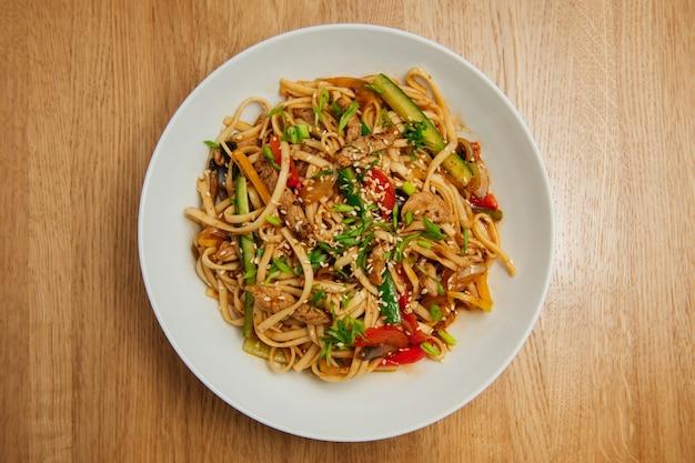 Azjatycki makaron z mięsem i warzywami w białym talerzu