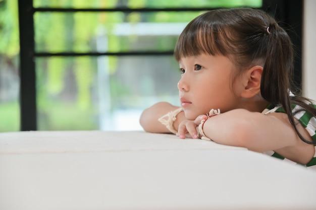 Azjatycki mała dziewczynka siedzi na stole patrząc smutno