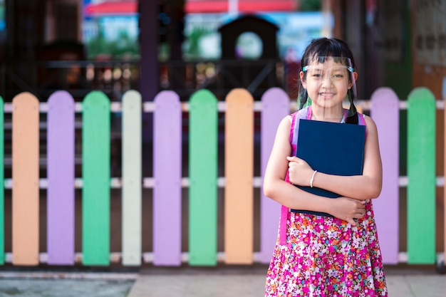 Azjatycki mała dziewczynka uczeń jest ubranym osłonę twarzy podczas gdy ona wraca do szkoły po kwarantanny covid-19.