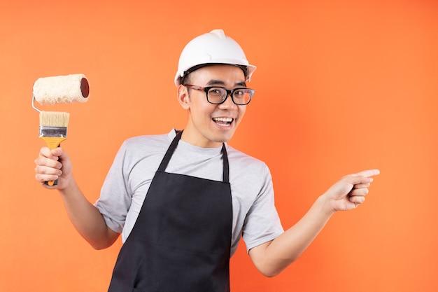 Azjatycki malarz trzymając pędzel pozowanie na pomarańczowej ścianie