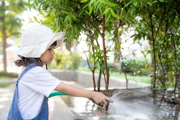 Azjatycki małe dziecko dziewczynka wylewanie wody na drzewach. koźlak pomaga pielęgnować rośliny za pomocą konewki w ogrodzie.
