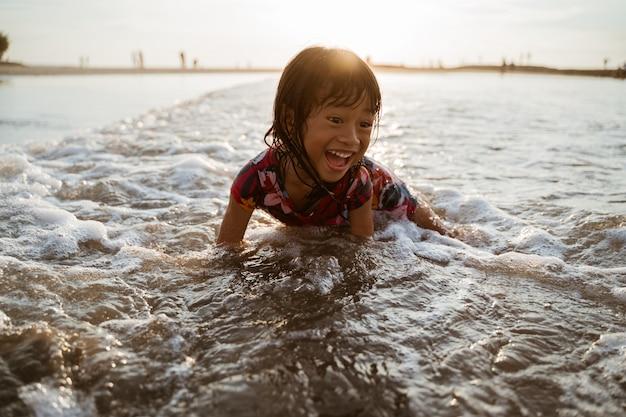 Azjatycki małej dziewczynki obsiadanie na piasku w plaży podczas gdy bawić się z wodą