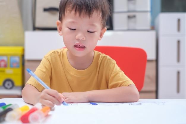 Azjatycki maluch chłopiec dziecko pisze / rysuje ołówkiem, student odrabiania lekcji, małe dziecko przygotowuje się do testu w przedszkolu