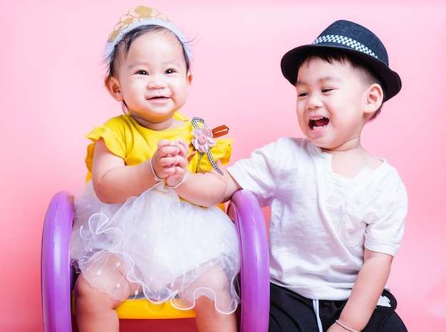 Azjatycki mały brat i jej dziewczynka w pięknej sukni siedzi na krześle