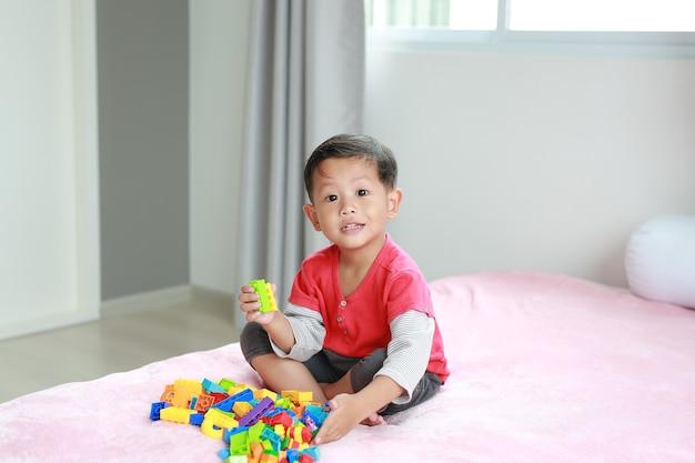 Azjatycki mały chłopiec bawi się w kolorowe plastikowe klocki i leżąc na łóżku.