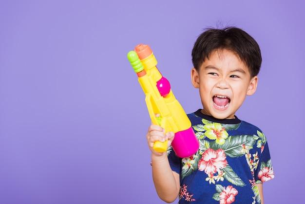 Azjatycki mały chłopiec trzyma plastikowy pistolet na wodę, tajlandia święto songkran
