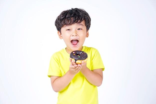 Azjatycki mały ładny chłopiec jedzenie duży pączek na białym tle