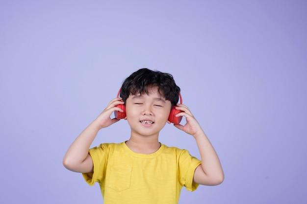 Azjatycki mały przystojny ładny chłopiec z słuchawkami do słuchania muzyki