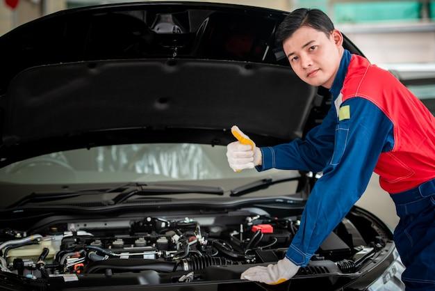 Azjatycki mechanik samochodowy w warsztacie samochodowym sprawdza silnik. w przypadku klientów korzystających z samochodów do napraw, mechanik będzie pracował w garażu.