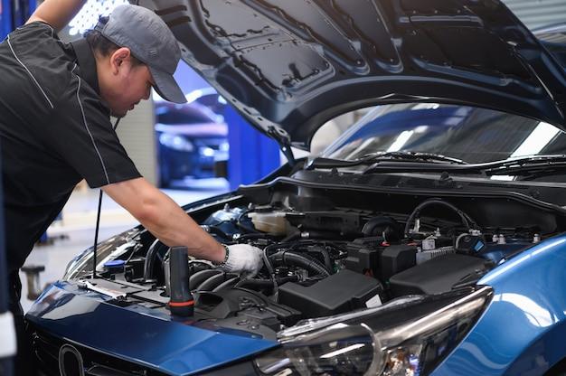 Azjatycki męski auto mechanik bada samochodowego problemu awarii silnika przed motoryzacyjnym
