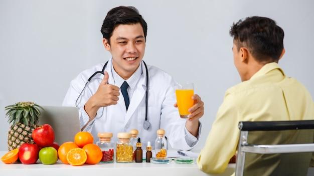 Azjatycki męski dietetyk uśmiecha się i gestykuluje kciukiem w górę, jednocześnie polecając sok pomarańczowy mężczyźnie w klinice