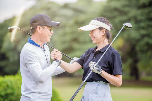Azjatycki męski i żeński golfista trząść ręki przy polem golfowym po gry