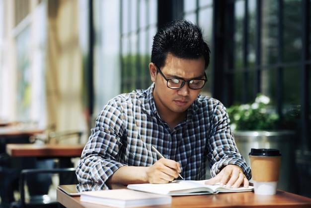 Azjatycki męski niezależny dziennikarz siedzi w plenerowej kawiarni i pisze w notatniku w szkłach