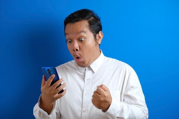 Azjatycki męski pracownik biurowy wygląda na pewnego siebie podczas dostępu do swojego smartfona, mężczyzna pokazuje zdziwiony wyraz twarzy