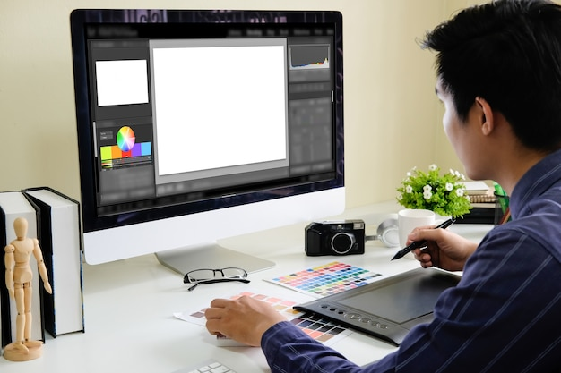 Azjatycki męski projektant używa grafiki pastylkę podczas gdy pracujący z komputerem przy studiiem lub biurem.