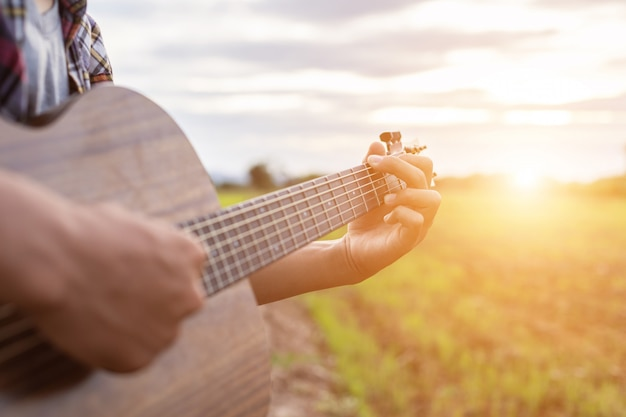 Azjatycki mężczyzna bawić się gitarę przy zielonym ryżu polem w zmierzchu czasie