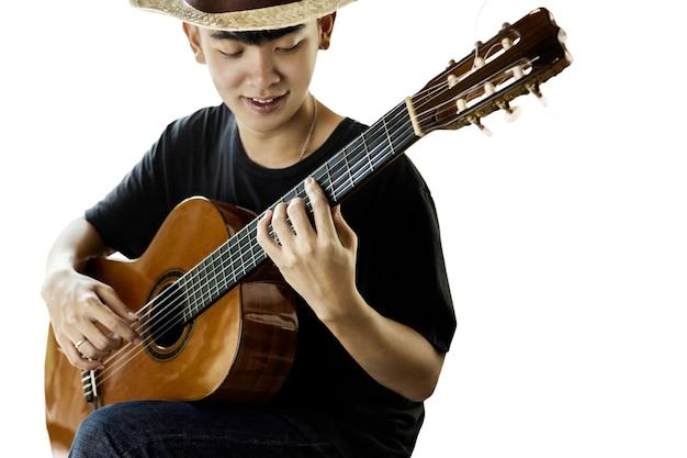 Azjatycki mężczyzna bawić się klasyczną gitarę odizolowywającą na bielu