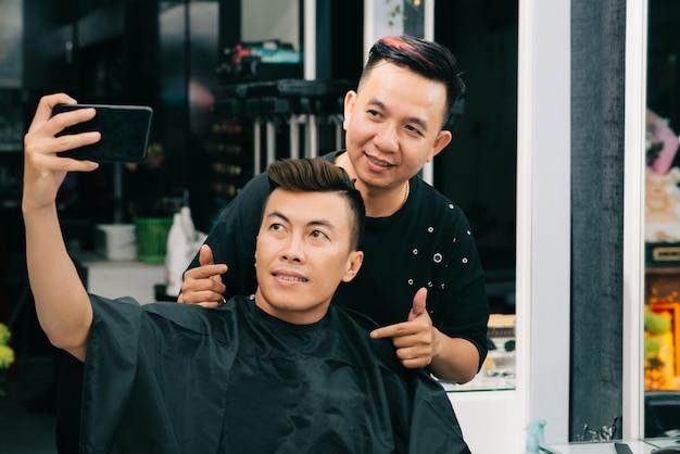 Azjatycki mężczyzna bierze selfie z jego fryzjerem w zakładzie fryzjerskim