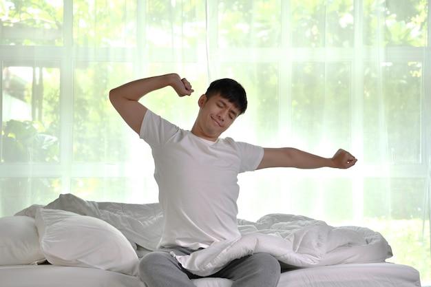 Azjatycki mężczyzna budzi się rano, siedząc na łóżku i rozciągając