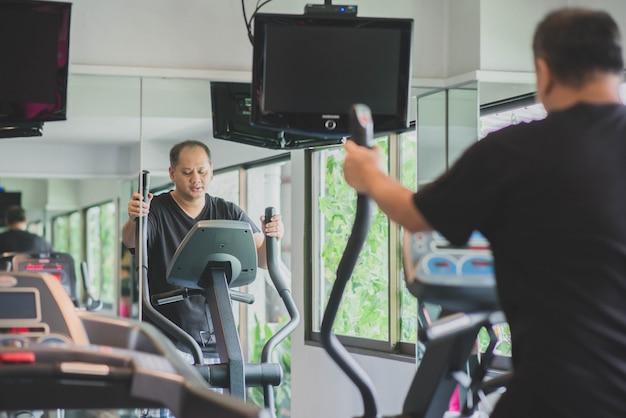 Azjatycki mężczyzna ćwiczy ćwiczenie przy gym odchudzaniem