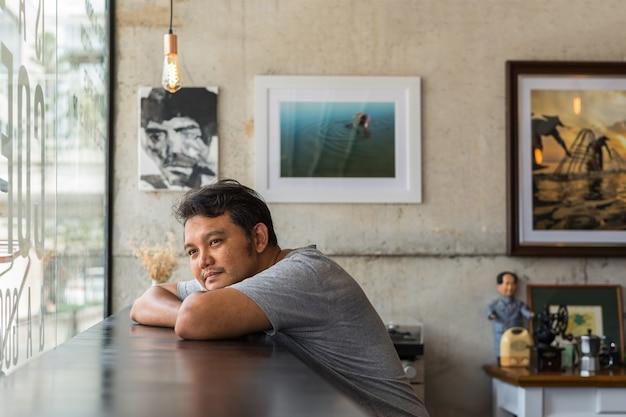 Azjatycki mężczyzna czekanie i brakujący kochanek w sklep z kawą