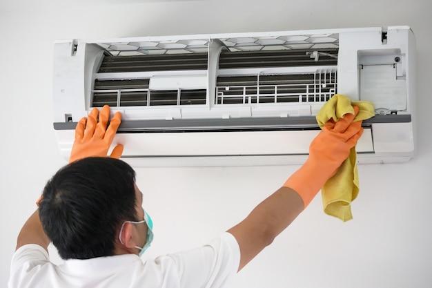 Azjatycki mężczyzna czyści klimatyzator ściereczką z mikrofibry